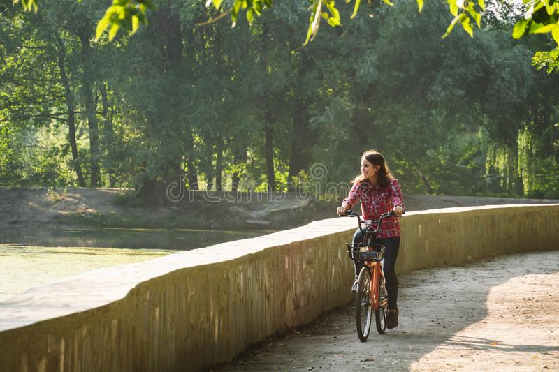 Subject ecological bicycle transport. Young Caucasian woman riding on a dirt road in a park near a lake renting an orange-colored royalty free stock photos