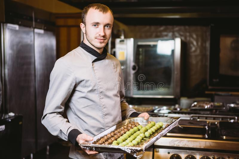Subject profession and cooking pastry. Young caucasian male pastry chef posing looking at camera in uniform in the kitchen holding. Sweets dessert candy truffle royalty free stock images