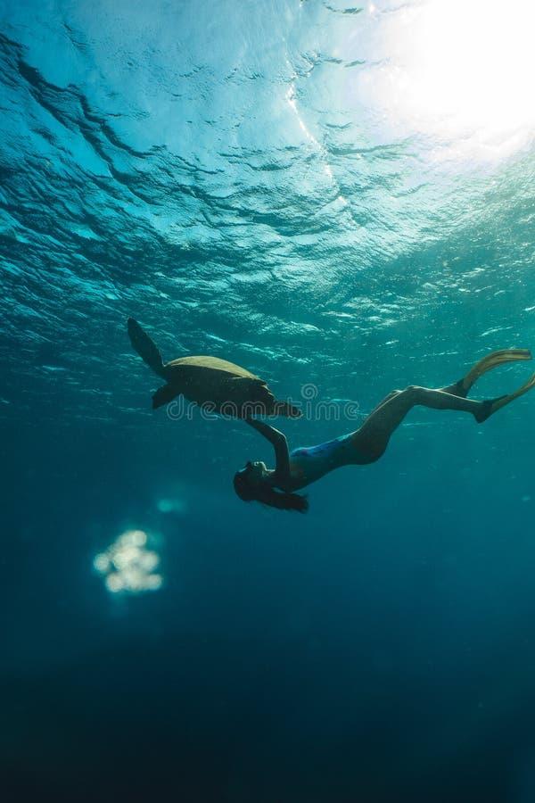 Submarino freediving de la muchacha con la tortuga linda en el mar azul fotos de archivo libres de regalías