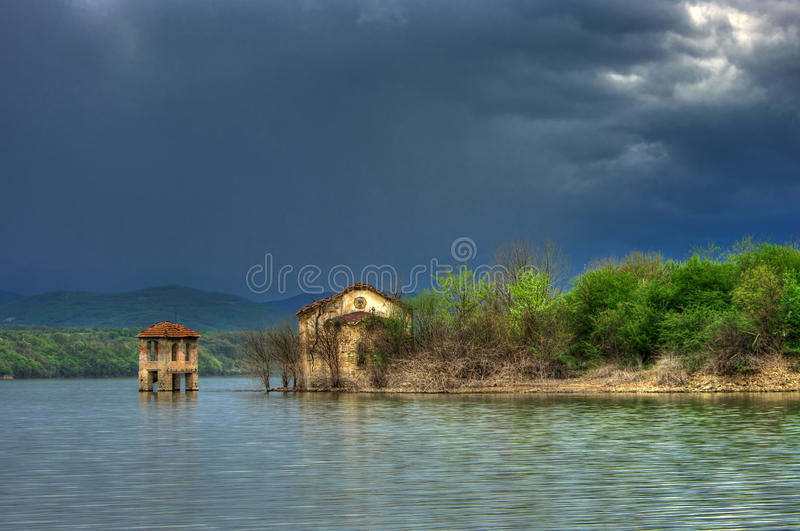 Submerged abandoned church in Ogosta dam, Bulgaria. Photo was taken in early spring. Amazing sky and interesting ruins on church Sveto Vaznesenie royalty free stock images