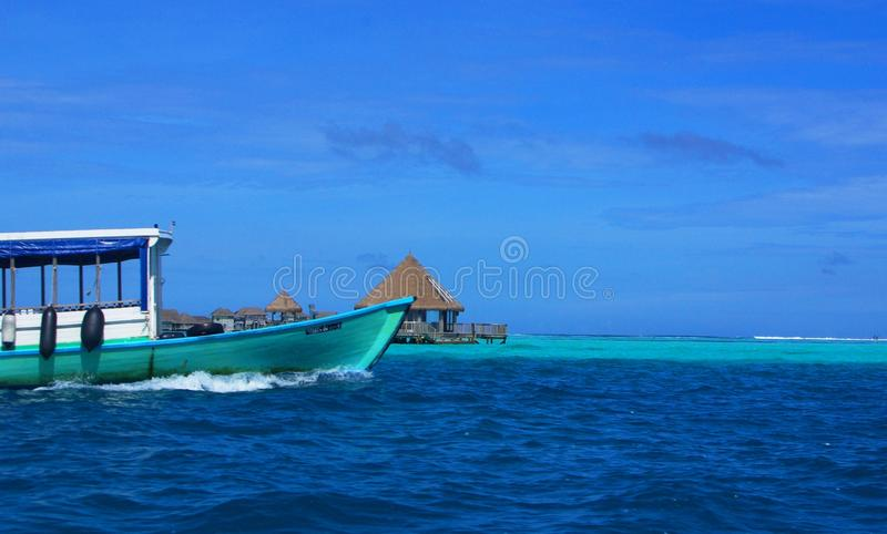 Submerged Atoll, Resort, Old Boat. An old boat passing a resort built onto a submerged atoll in the Maldives Male Atoll stock image
