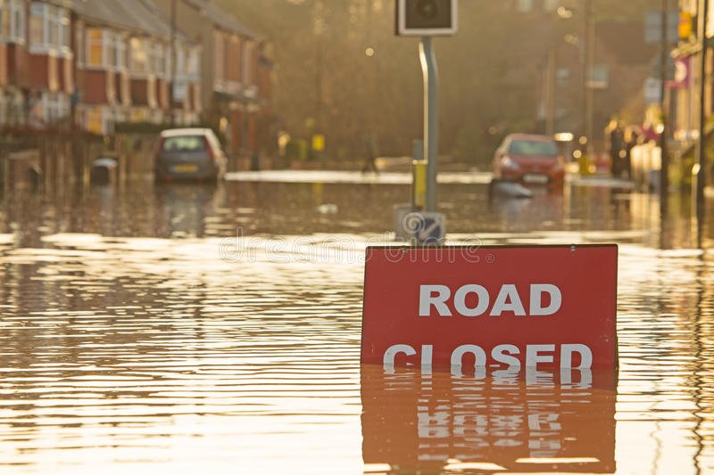Submerged Road Closed sign. A 'Road Closed' sign partially submerged by flood water with flooded streets beyond stock photos