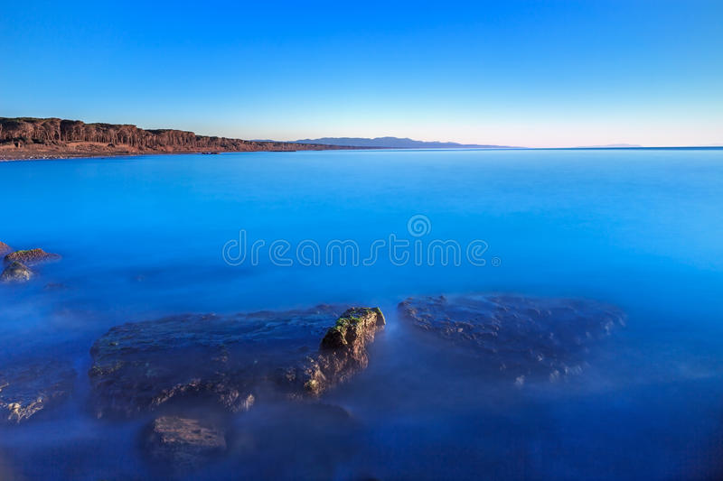 Submerged rocks, blue ocean, clear sky on bay beach sunset. Submerged rocks in a blue ocean, under a clear sky on a bay beach on sunset. Pine forest on stock image