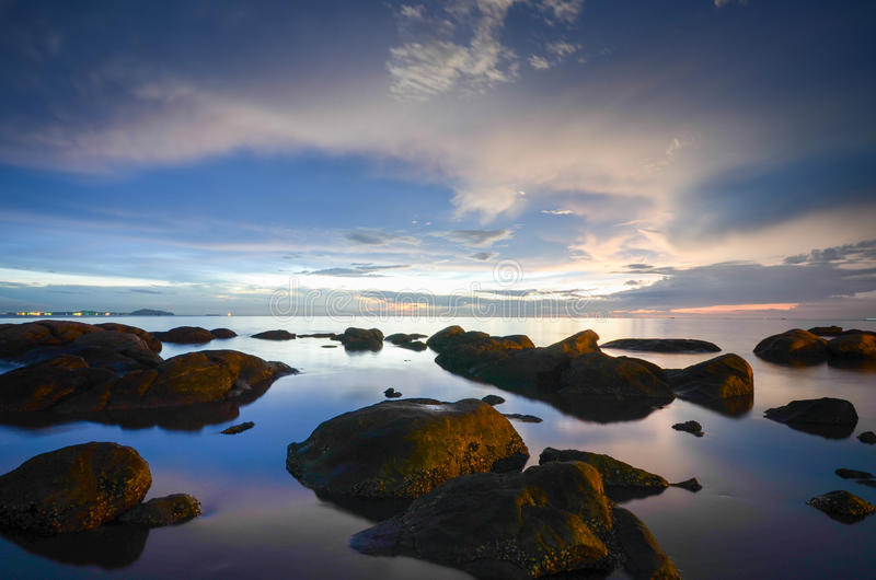 Submerged rocks in the sea under red skies. Submerged rocks in the sea under red cloud filled skies royalty free stock photos