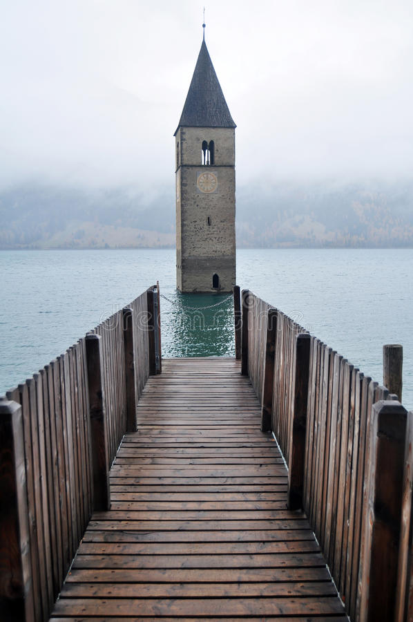 Submerged tower of reschensee church deep in Resias Lake of Bolzano or bozen at Italy. Submerged tower of reschensee church deep in Resias Lake in Trentino-Alto royalty free stock photography