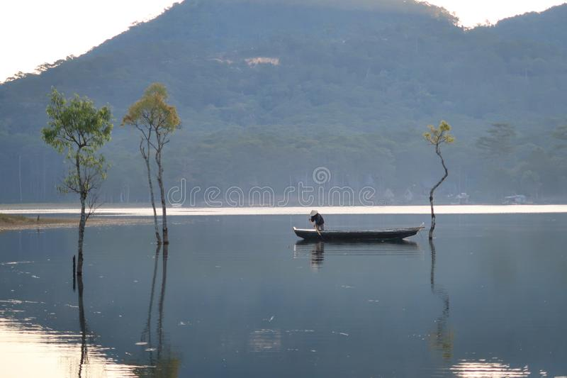 Flooded forest reflection on the lake with boatman in magic light part 33. Submerged trees with green fresh leaves reflecting on the lake and the boatman at royalty free stock photography