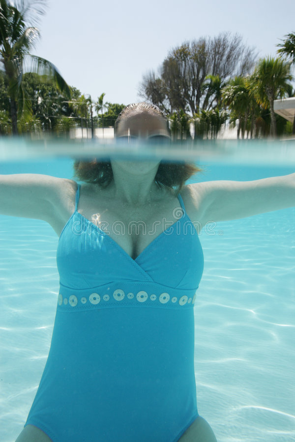 Submerged woman. A view of a submerged woman in a blue swimsuit in the pool water stock image