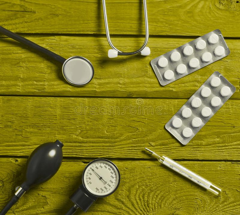 Subministros médicos na tabela de madeira colorida Estetoscópio, tabuleta, termômetro fotografia de stock royalty free