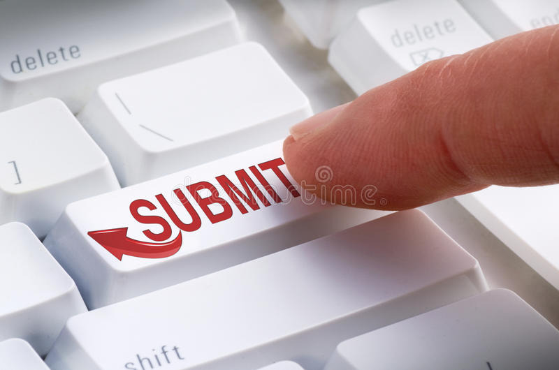 SUBMIT Keyboard Button Online Submission. Closeup of a big SUBMIT button on a keyboard with a finger getting ready to hit it and make a online submission royalty free stock photos