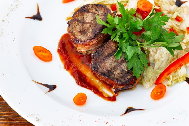 Subordonné juteux de biftek de boeuf rare moyen avec de la sauce d'un plat blanc photos libres de droits