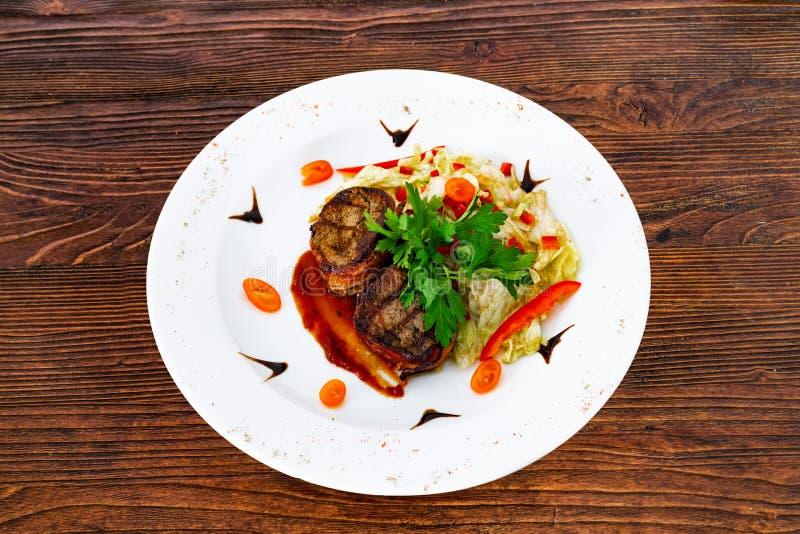 Subordonné juteux de biftek de boeuf rare moyen avec de la sauce d'un plat blanc image libre de droits