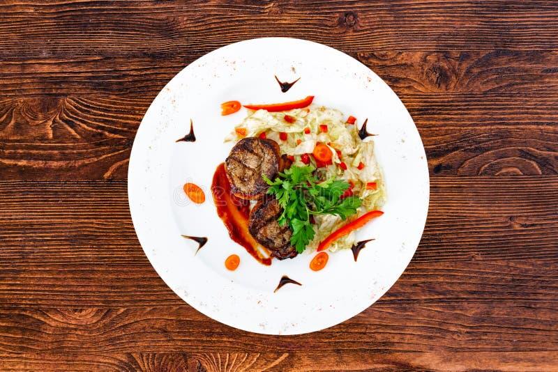 Subordonné juteux de biftek de boeuf rare moyen avec de la sauce d'un plat blanc photos stock