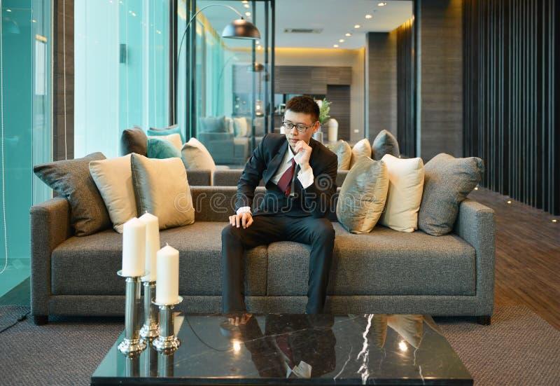 Subrayan al hombre asiático del negocio hacia fuera y nervioso, pensando en el sofá imagen de archivo libre de regalías