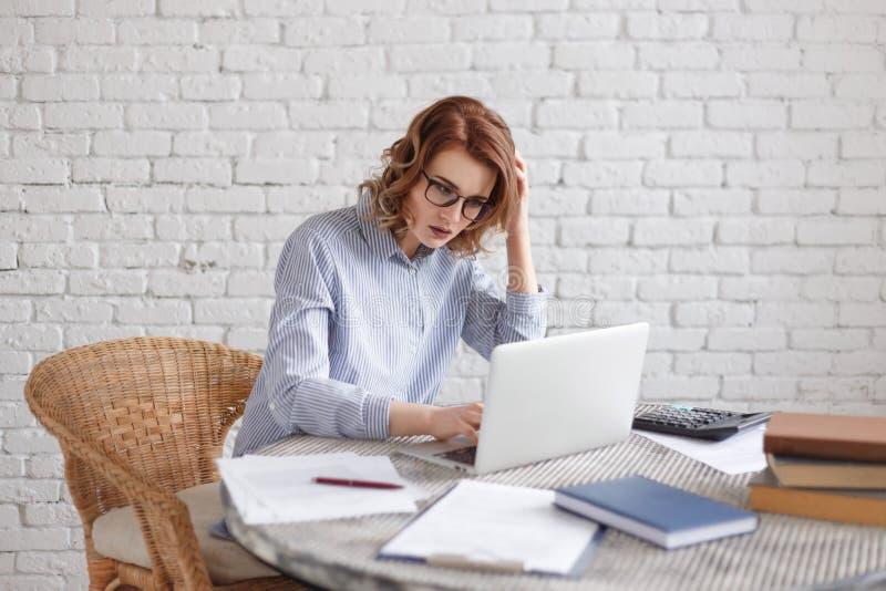 Subrayan a las mujeres en el trabajo en la oficina La mujer de negocios muy seria delante de su ordenador portátil en la oficina fotos de archivo libres de regalías
