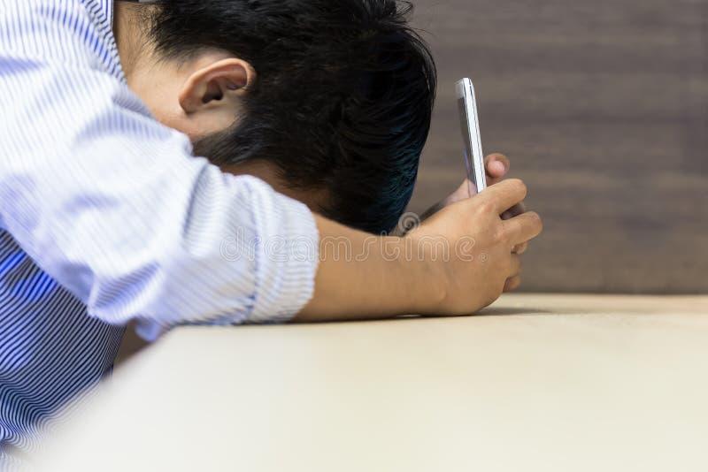 Subraye al hombre de negocios que sostiene el teléfono elegante en la tabla de madera BU en línea foto de archivo