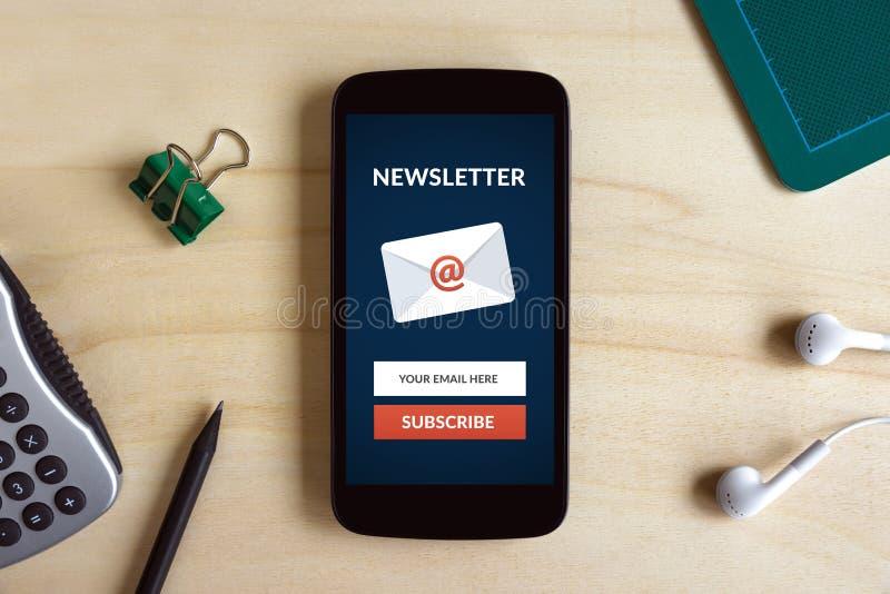 Subscreva o conceito do boletim de notícias na tela esperta do telefone no DES de madeira imagem de stock royalty free