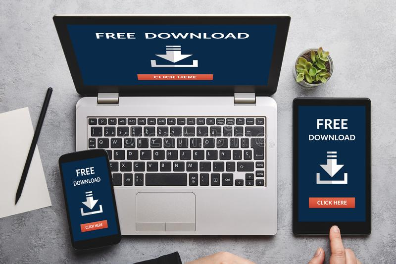 Free download concept on laptop, tablet and smartphone screen. Over gray table. All screen content is designed by me. Flat lay royalty free stock photos