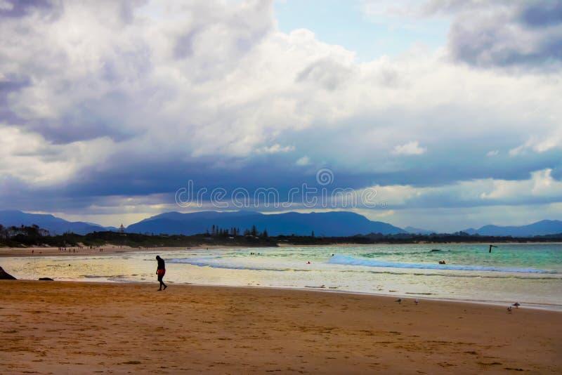 Subsidence d'homme - fatiguée ou triste - marchant sur la plage sortant du ressac à l'heure d'or avec la plage pleine des personn photo stock