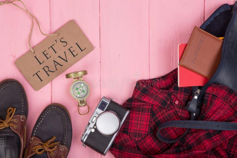 Substance de touristes - sac, passeport, caméra, boussole, chaussures, chemise, bloc-notes et tableau noir avec le texte Let' photographie stock libre de droits