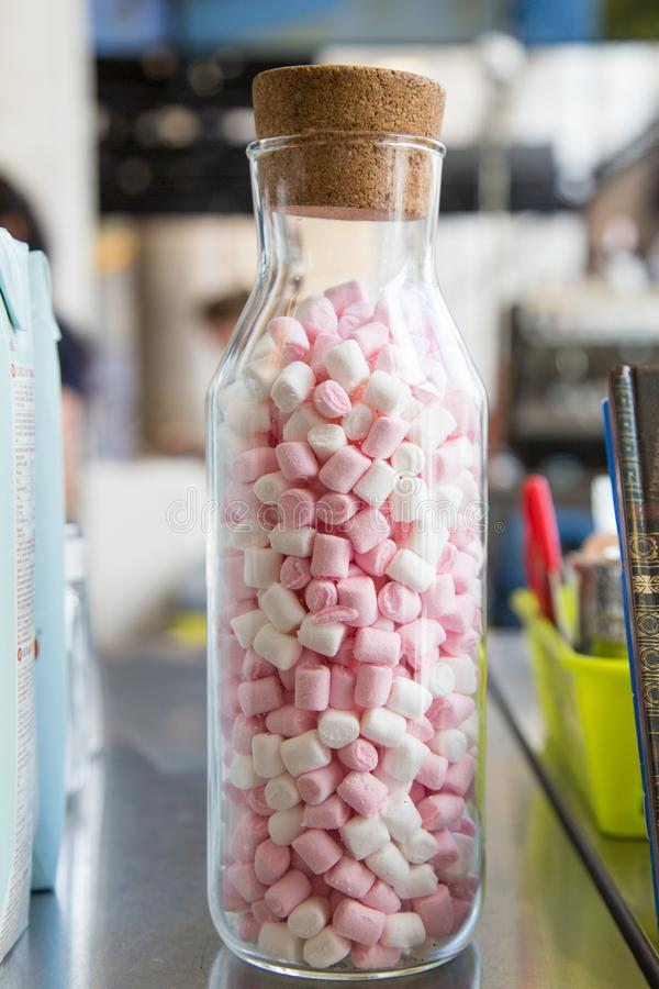 Substitua o rosa do açúcar em uma garrafa de vidro com um bujão imagem de stock