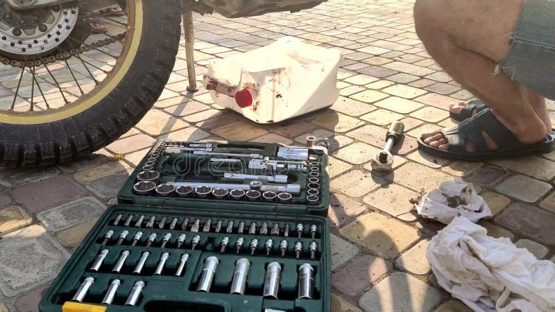 Substituição do óleo de lubrificação em uma motocicleta o homem drena sujo desperdiça o óleo de uma motocicleta imagens de stock royalty free