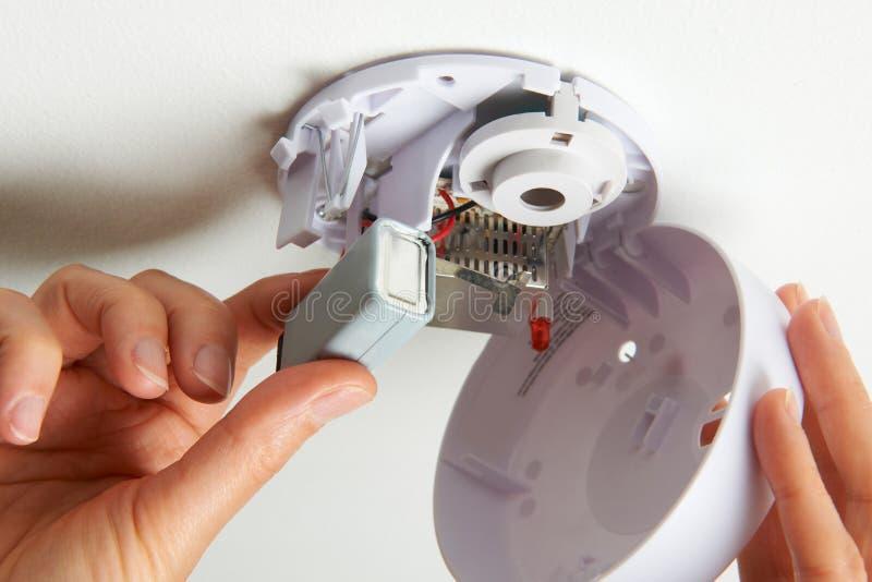 Substituindo a bateria no alarme de fumo doméstico fotografia de stock
