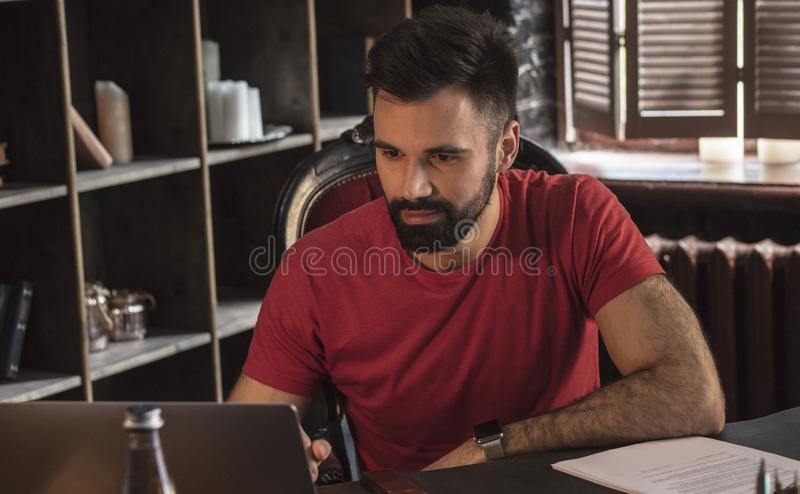Young businessman with beard sitting in chair and working on laptop on table royalty free stock photo