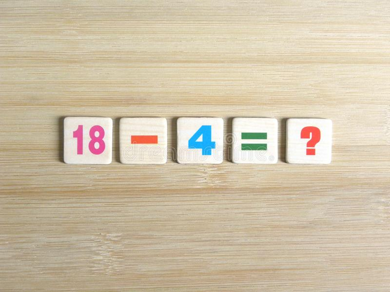 Subtract two numbers. Subtraction of two whole numbers 18-4=? on wood background royalty free stock images