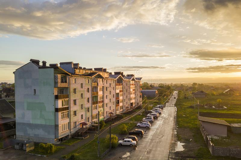 Suburb landscape, apartment building. Parked cars along bad road on spring day on blue sky copy space background.  royalty free stock photography