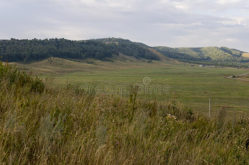 Suburb and villages. Big mountains and green forests. Trees and their shadows on the grass. Summer day with dark blue and grey sky. And  clouds. Fields. Fresh royalty free stock image