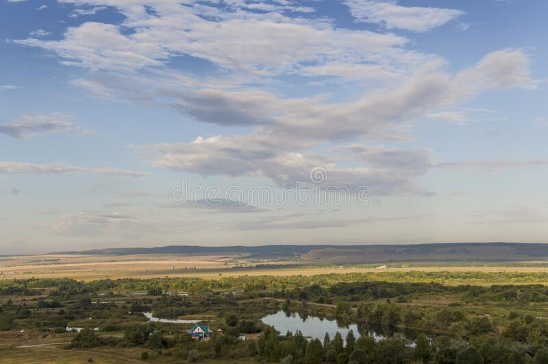 Suburb and villages. Big mountains and green forests. Trees and their shadows on the grass. Summer day with dark blue and grey sky. And  clouds. Fields. Fresh stock photo