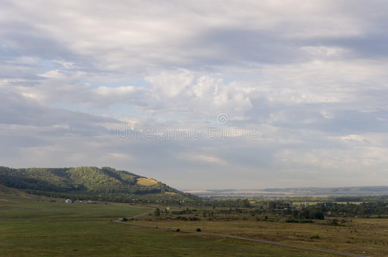 Suburb and villages. Big mountains and green forests. Trees and their shadows on the grass. Summer day with dark blue and grey sky. And  clouds. Fields. Fresh royalty free stock images