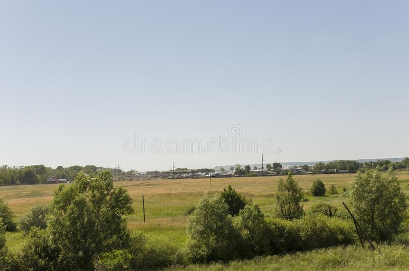 Suburb and villages. Big mountains and green forests. Trees and their shadows on the grass. Summer day with dark blue and grey sky. And  clouds. Fields. Fresh stock photography