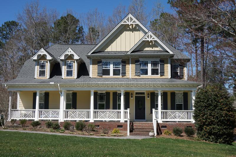 Suburban home with a yellow exterior and a large porch stock images