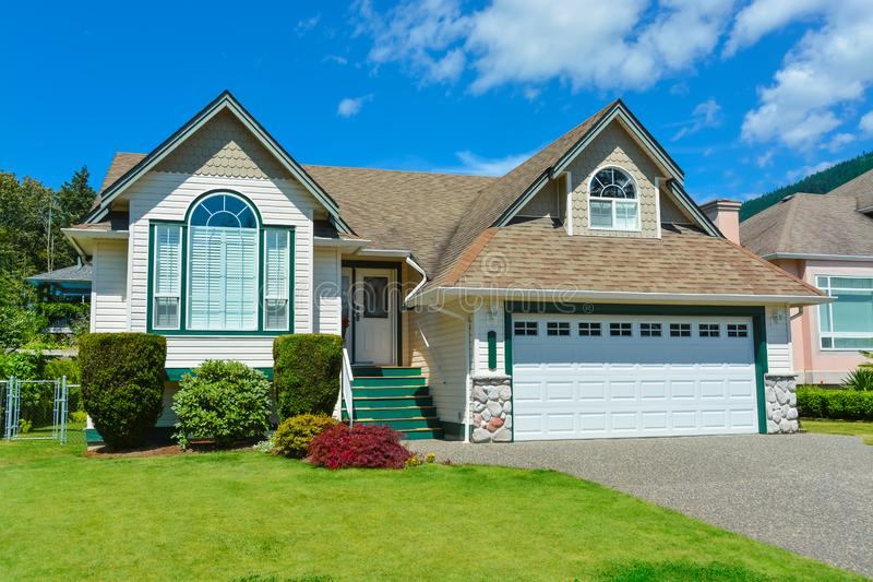 Suburban house with concrete driveway and blue sky background. House for sale stock image
