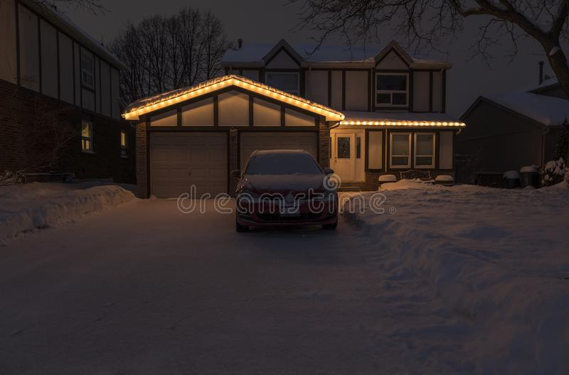 Suburban House Lit With Christmas Lights After a Snow Fall. Night Scene of a Suburban House with Christmas Lights and Covered with a Blanket of Snow royalty free stock images