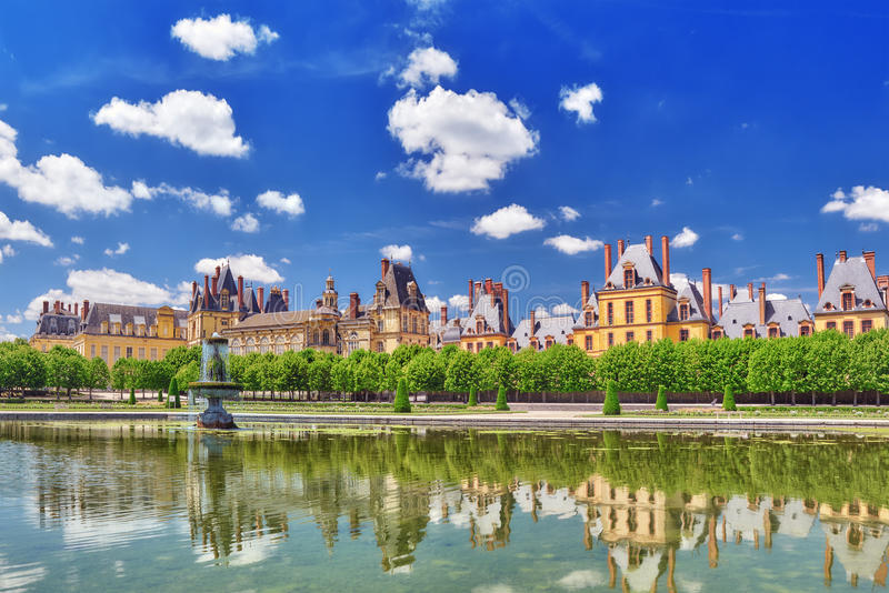 Suburban Residence of the France Kings - beautiful Chateau Fontainebleau with the fountain on foreground. royalty free stock image