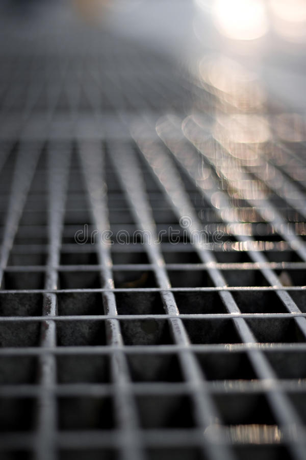 Subway Grate. Closeup of a sidewalk subway grate with shallow depth of field stock image
