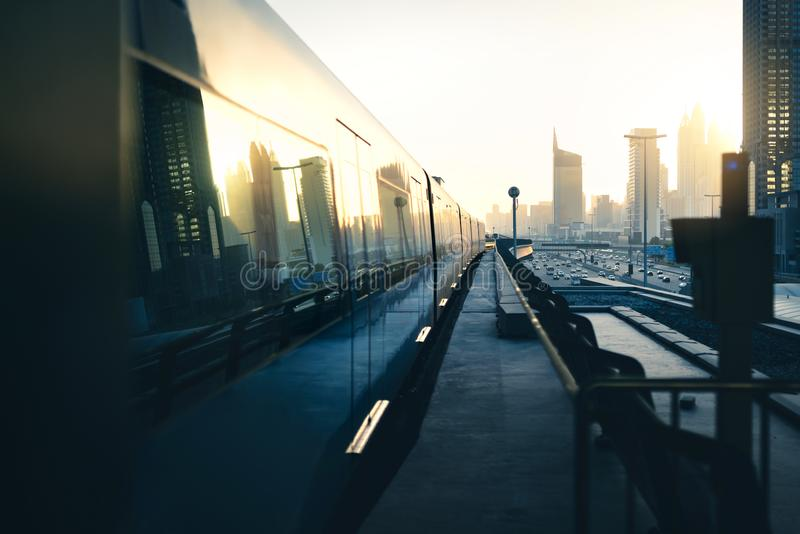 Subway and metro train in city. Futuristic modern public transport. Dubai railway system at sunset with skyscraper buildings. Subway and metro train in city stock photography