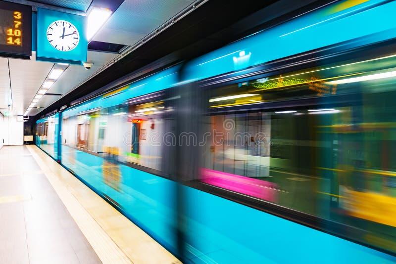 Subway metro train at railway station platform with motion blur stock photo