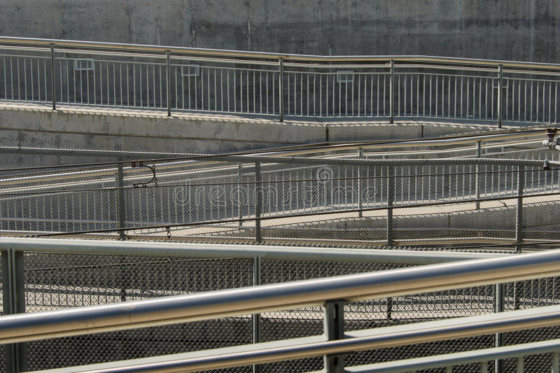 Subway Ramps and Handrails. Pedestrian ramps and handrails descend to right, left and right again to urban subway station. Strong overhead light casts complex royalty free stock photography