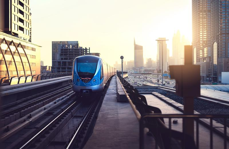 Subway train at sunset in modern city. Dubai metro. Downtown skyline with sundown. Skyscraper buildings and car traffic. stock photo
