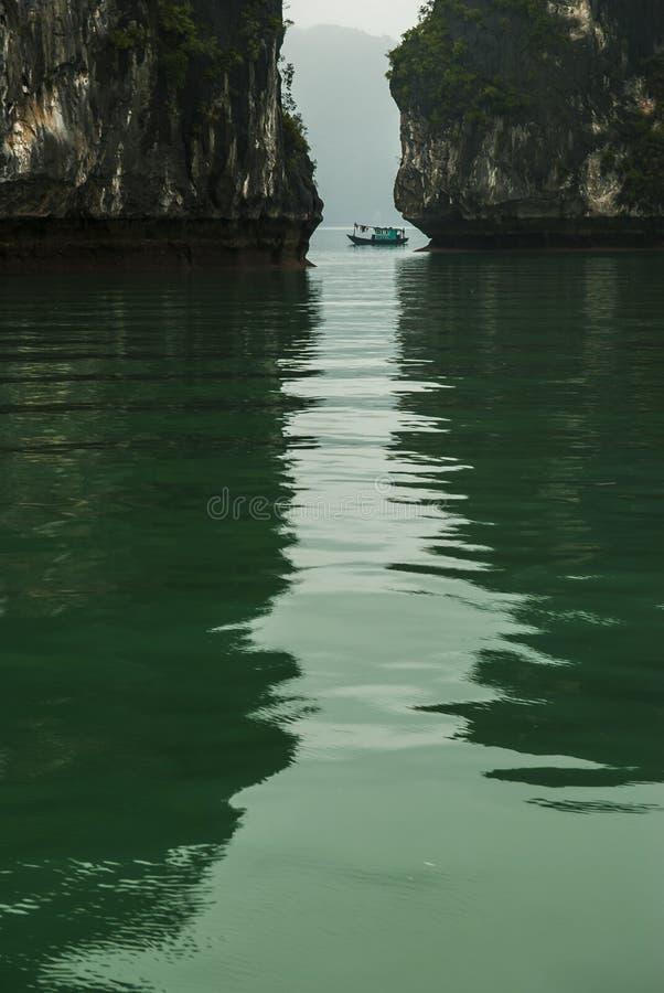 A sucata do turista passa a diferença nas rochas na baía longa do Ha imagem de stock royalty free