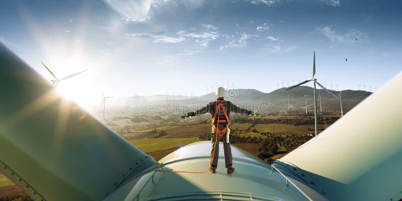 Succès heureux de sensation d'ingénieur après bon travail Il tenant un dessus de moulin à vent et semblant le beau coucher du sol image libre de droits