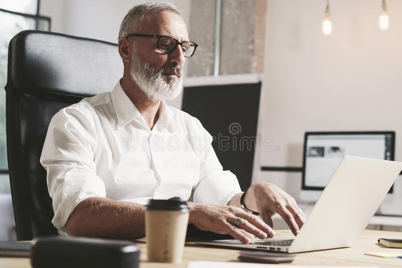 Succes and confidental adult businessman using mobile laptop computer while working at the wooden table at modern stock photo