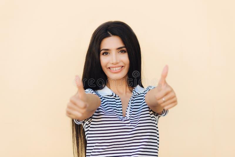 Succes en goedkeuringsconcept Het positieve wijfje met zwarte het lange haar, prettige glimlach heeft, houdt duimen omhoog, houdt stock afbeelding