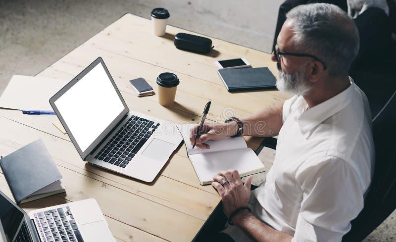 Succes en vertrouwelijke volwassen zakenman die mobiele laptop computer met behulp van terwijl het werken bij de houten lijst bij stock foto