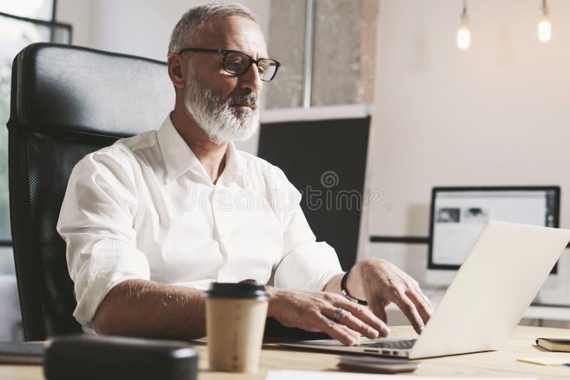 Succes et homme d'affaires adulte confidentiel utilisant l'ordinateur portable mobile tout en travaillant à la table en bois à mo photo stock