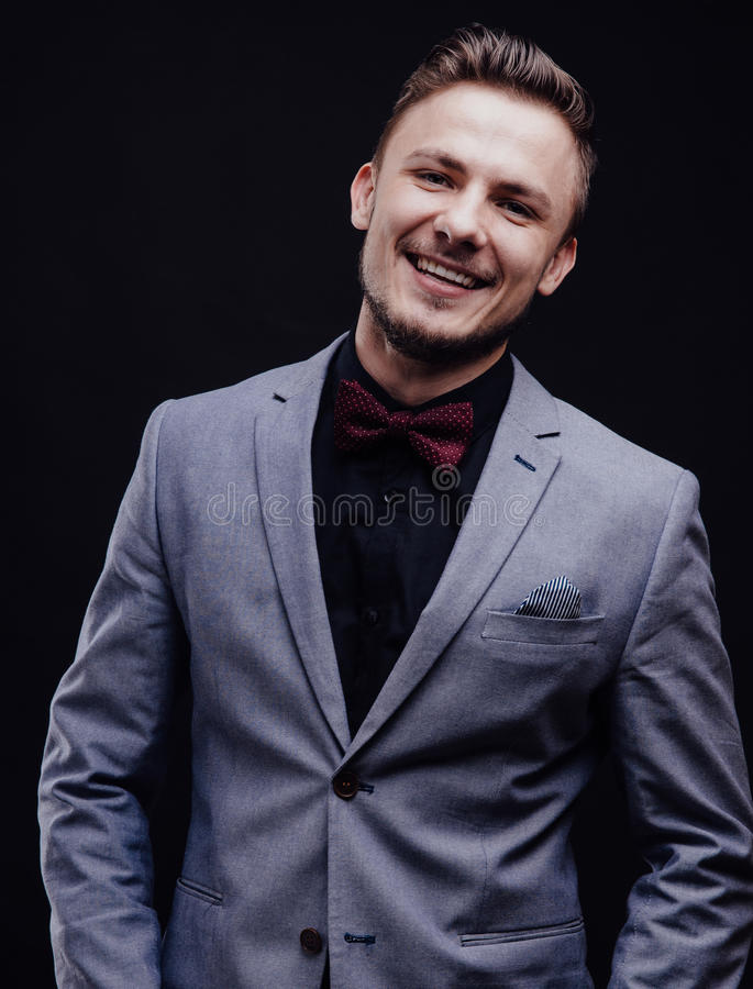 Succes guy in gray jacket looking with butterfly smiling on dark background stock image