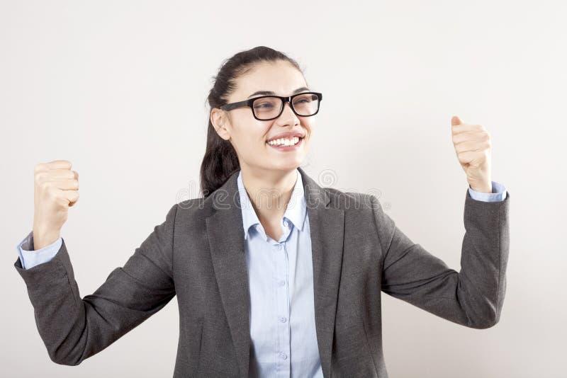 Succes in zaken of carrière Enthousiaste onderneemster die met opgeheven wapens in geïsoleerd op grijze achtergrond toejuichen stock fotografie